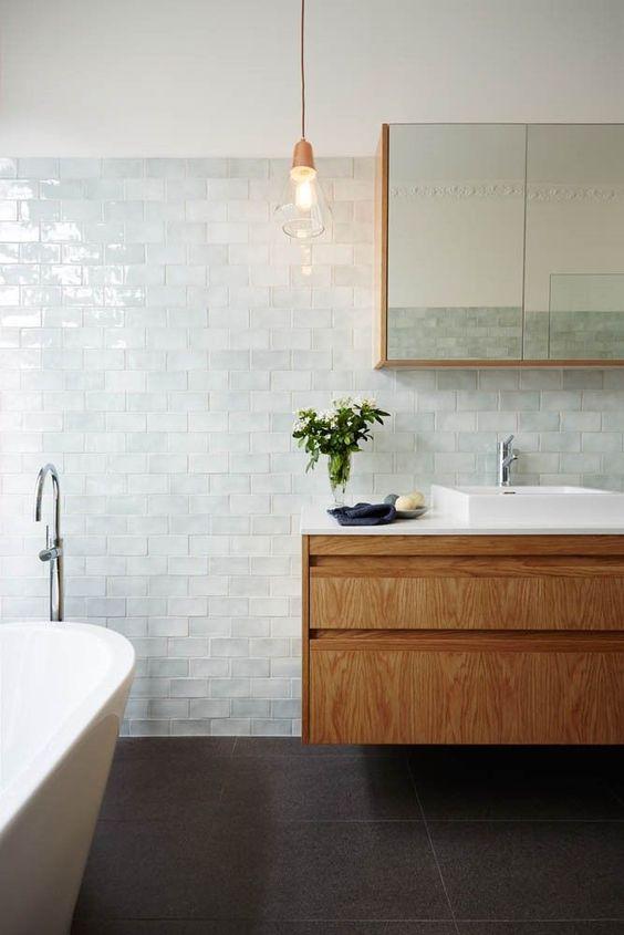 Banheiro com piso escuro e azulejo branco texturizado