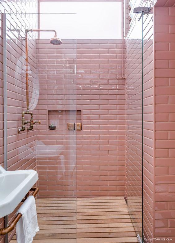 Banheiro com revestimento rosa e metais bronze