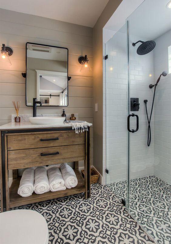 Banheiro com piso desenhado e azulejo branco