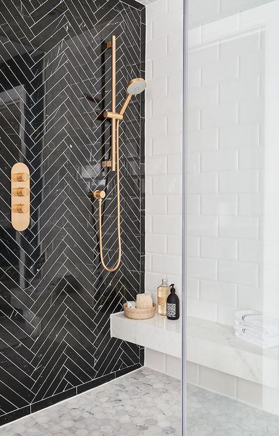 Banheiro com azulejo preto e branco e metais dourados