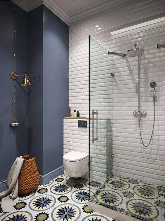 #29- Banheiro com piso colorido com pintada de azul e tijolinho branco. Composição bonita e divertida.