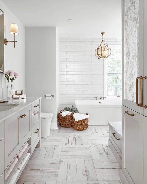 banheiro com banheira e revestimento branco com piso claro