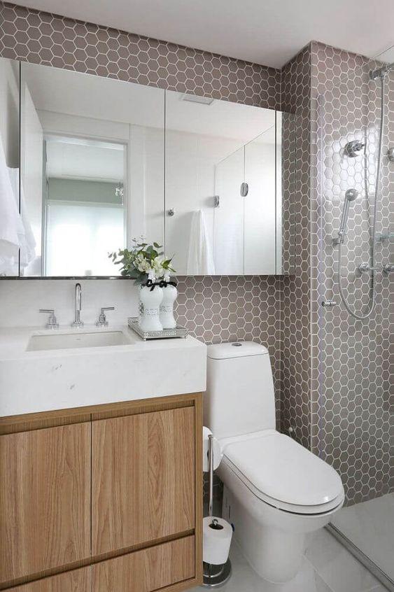 Banheiro com pastilha hexagonal cinza, bancada branca e marcenaria em madeira 39 banheiros pequenos para você se inspirar