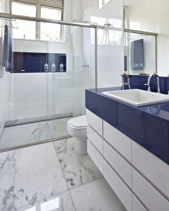Bancada e nicho coloridos com revestimento branco nas paredes e mármore no piso