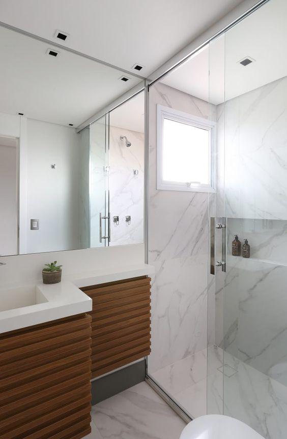 Banheiro com porcelanato que imita marmore carrara  e movel de madeira