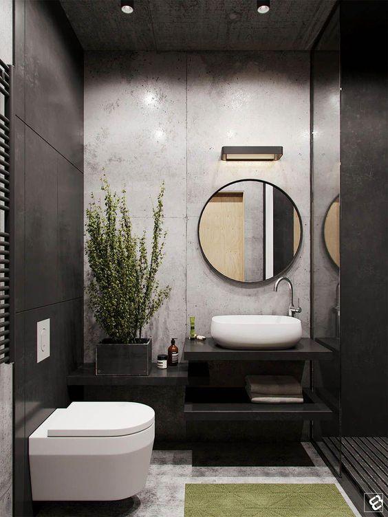 Banheiro com cimento queimado e revestimento preto. Vaso suspenso