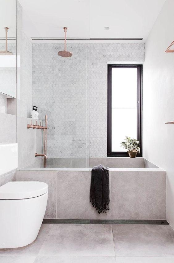Banheiro com  banheira de alvenaria revestida de porcelanato, revestimento marmorizado hexagonal e metais bronze.