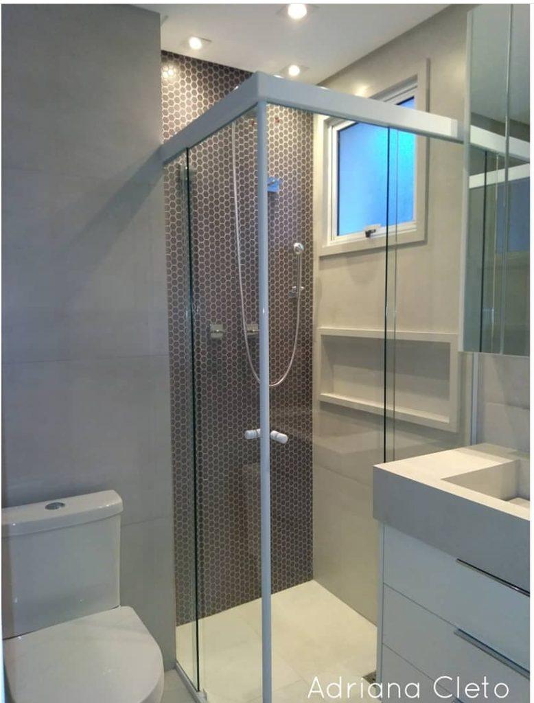 Banheiro com pastilha hexagonal grafite e porcelanato cinza claro.
