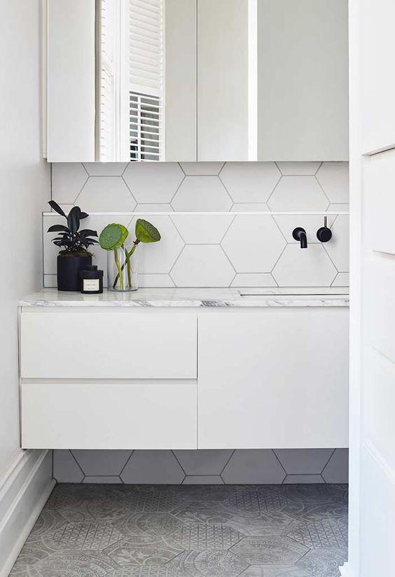 banheiro com revestimento hexagonal branco e cinza. E moveis brancos.