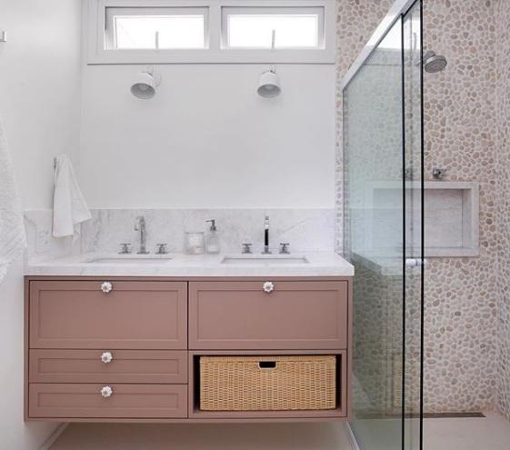 banheiro com seixos brancos e moveis rosa