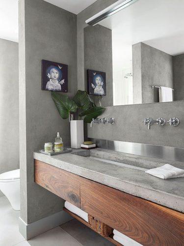 Banheiro com piso, parede e bancada de cimento queimado