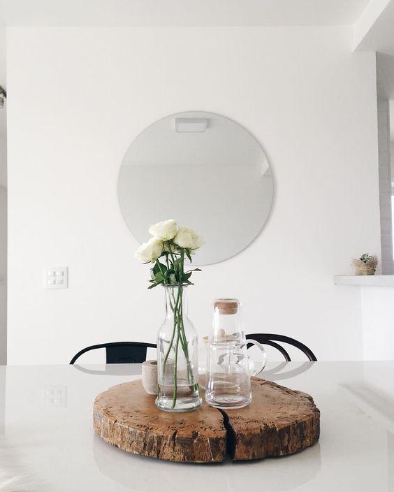 sala estilo escandinavo com mesa branca, tronco de madeira no centro da mesa, garrafas transparentes com flores
