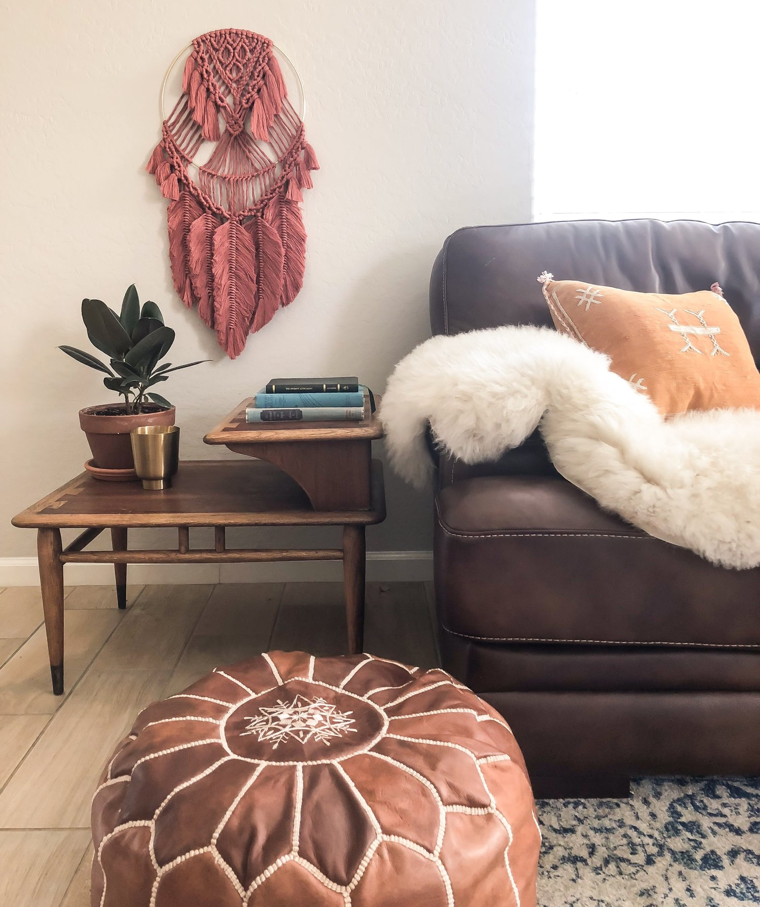 Sala de estar com: sofá, almofadas e mesinha em estilo boho. na parede existe uma exuberante mandala vermelha.