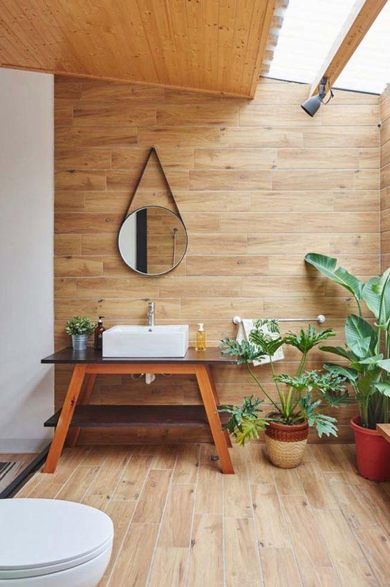 Neste banheiro, o porcelanato que imita madeira foi utilizado na parede e piso mas em sentido diferente.