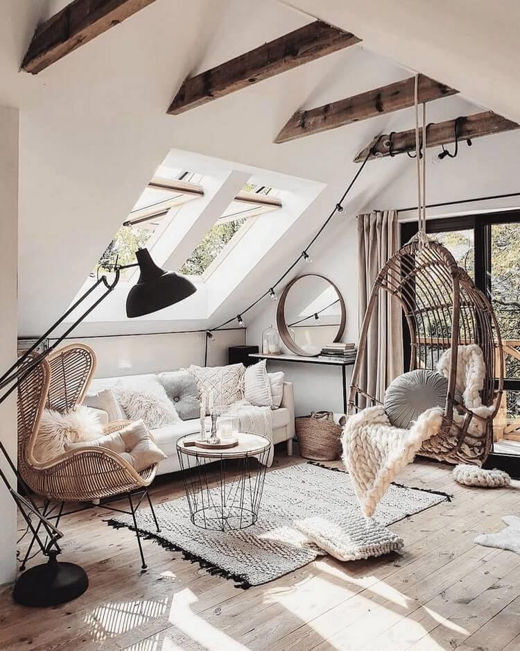 Sala de estar com sofá branco, almofadas com tecido cashmere, tapete com tecido casmere, balanço suspenso de madeira, e piso de porcelanato com efeito madeira.