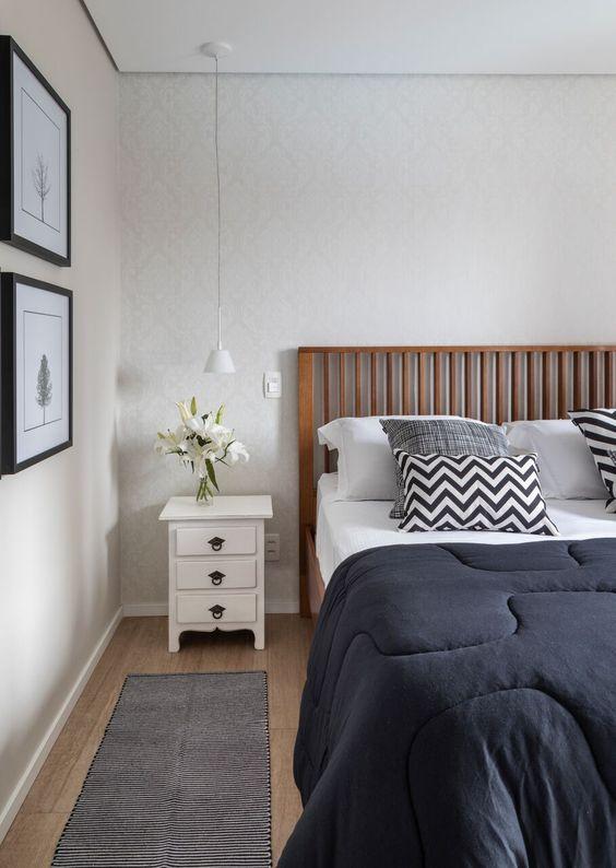 quarto com papel de parede claro, cama de casal de madeira com roupa de cama cinza e branca, criado-mudo branco e no piso foi utilizado porcelanato que imita madeira.
