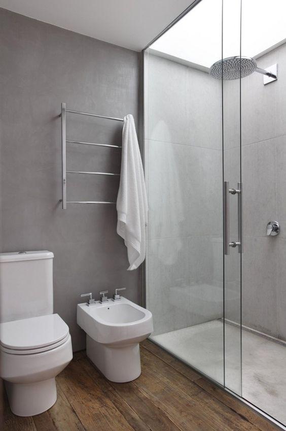 banheiro revestido com porcelanato cinza na parede e porcelanato que imita madeira no chão. Nesta imagem temos uma privada branca e bidê branco com um boxe de vidro.