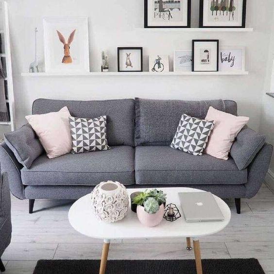 32 ideias inspiradoras para usar porcelanatos na sala Sala de estar com porcelanato que imita madeira pátina. Nesta sala de estar existe: uma prateleira com quadros, um sofá estofado cinza e uma mesinha branca com pés de madeira.