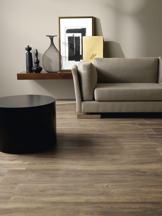Sala com decoração minimalista e cores neutras. bacão e sofá ao fundo, e à esquerda uma mesa redonda preta. No piso foi utilizado porcelanato que imita madeira.