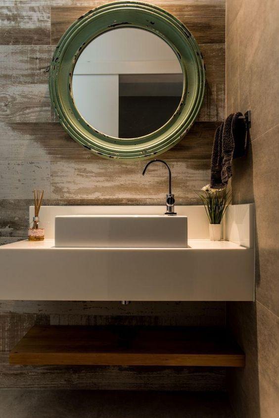 banheiro com lavabo branco, espelho com moldura redonda e revestimento das paredes em porcelanato que imita madeira pátina.