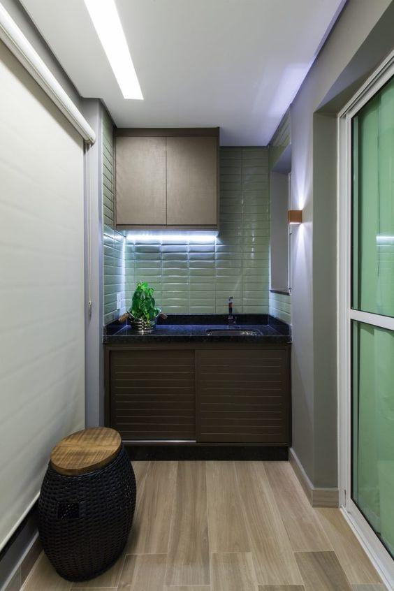 Lavanderia com armários em cores escuras, azulejo subway verde nas paredes e porcelanato que imita madeira no piso.