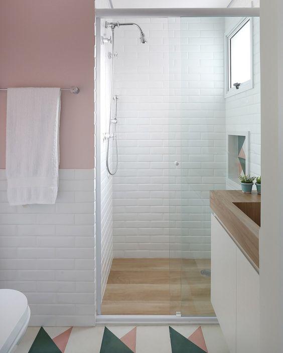 Banheiro com cores claras. azulejo subway branco nas paredes e porcelanato que imita madeira dentro do box.