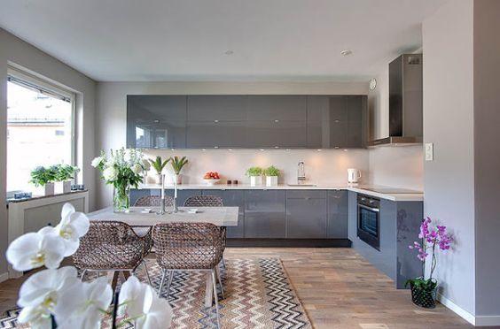 Cozinha com sala de jantar integrado. mesa mármore claro e cadeiras trançadas ao centro. armário cinza. Porcelanato claro nas paredes e porcelanato que imita madeira no piso.