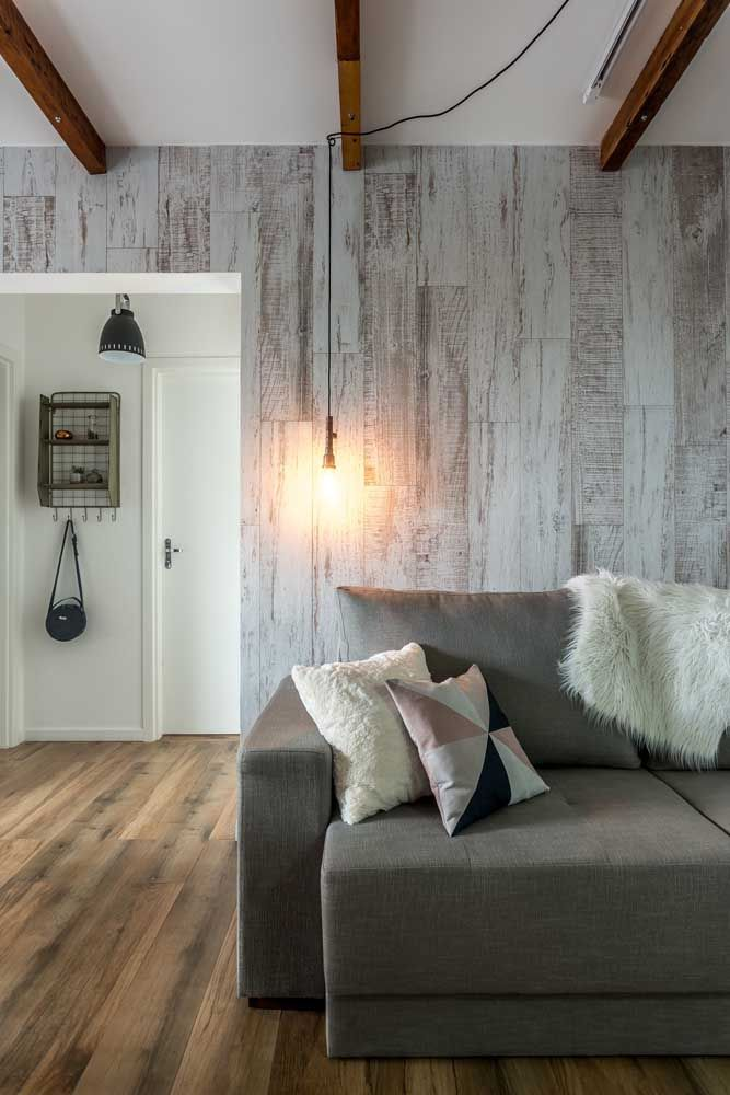 Sala de estar pequena com um sofá cinza. Foram usados porcelanatos com efeito madeira nas paredes e piso, mas com tonalidade mais clara para não pesar.