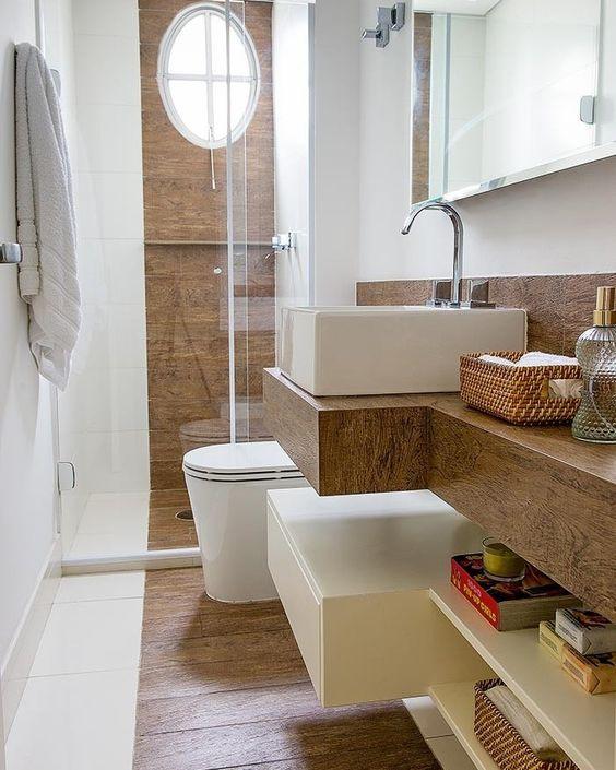 Revestimento de madeira aparece em faixa ao fundo e piso do Box e na bancada de porcelanato que imita madeira.