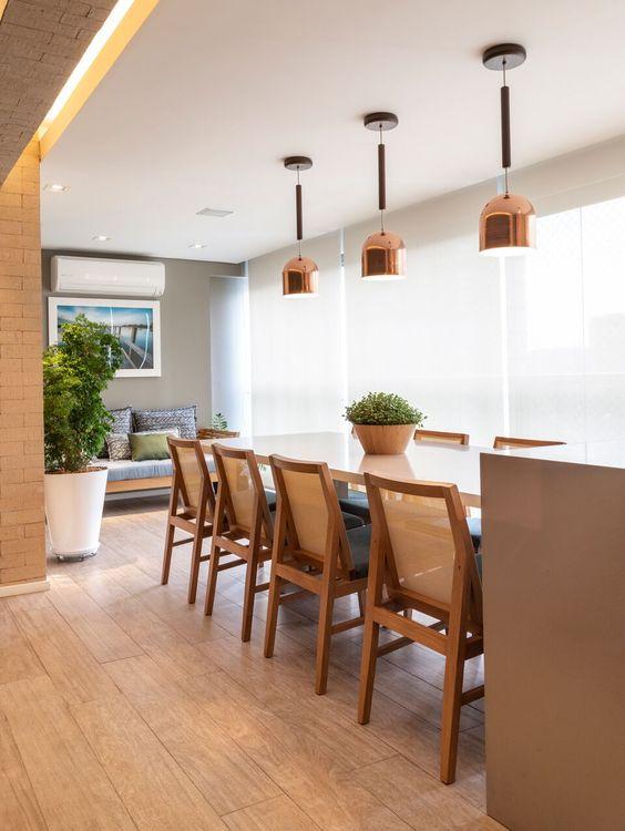 varanda ampla, com: mesa, cadeiras de madeira e no piso foi utilizado porcelanato que imita madeira.