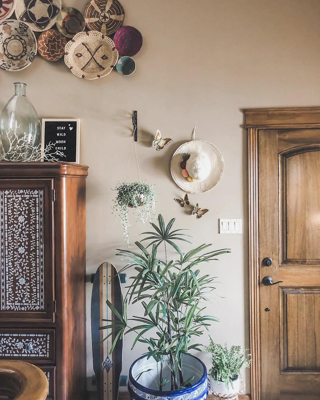 Armário de madeira com detalhes florais, pratos na parede com detalhes étnicos e um vaso de plantas de cor azul. Estilo Boho.