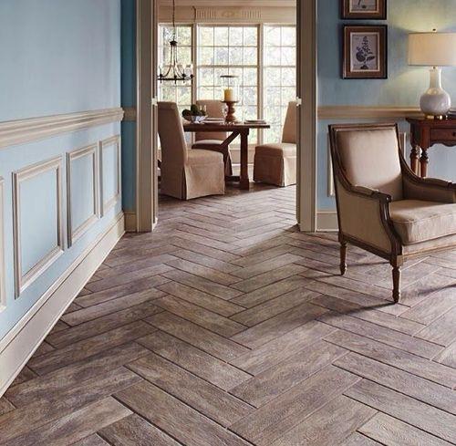 Sala com um ar clássico na decoração com cadeiras e objetos antigos. Parede turquesa com detalhes emoldurados e piso de porcelanato que imita madeira.