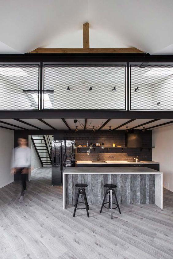 Loft, com: balcão revestido de porcelanato madeira, parede do fundo revestida de tijolinhos pretos, movéis pretos, paredes laterais brancas e um mezanino com paredes brancas e metais pretos. O piso é de porcelanato que imita madeira.