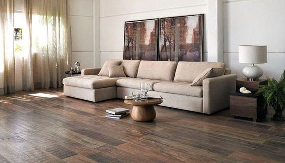 Sala ampla com cores neutras. Sofá ao fundo, uma mesinha redonda no centro com outras duas mesinhas nas laterais do sofá, todas em tons de marrom. A parede é branca com duas linhas horizontais e o piso é porcelanato  com efeito madeira.