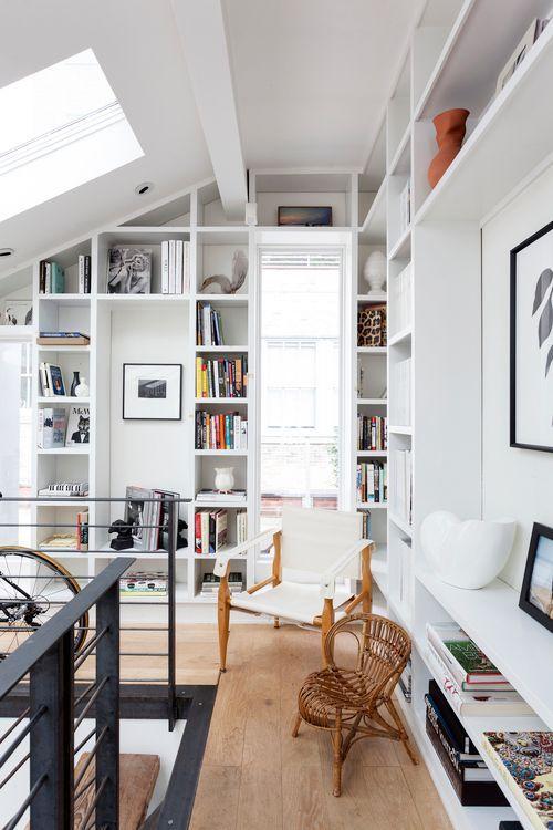 Quarto totalmente branco com inúmeras prateleiras que vão do chão ao teto,  uma cadeira de madeira branca e uma cadeira trançada de madeira. o piso utilizado foi porcelanato que imita madeira.