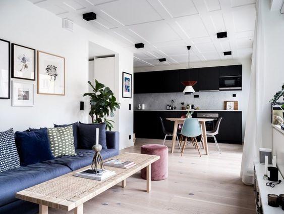 Sala de estar integrada com a cozinha. Foram utilizados branco e preto para dar um contraste clássico. Existe um armário preto ao fundo com uma mesa de madeira, e um sofá azul escuro na lateral da sala de estar. As paredes são brancas e o piso é porcelanato que imita madeira.