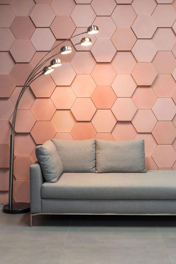 Sala de estar com um sofá e abajur de cores neutras. Na parede foi utilizado porcelanato com efeito 3D de cor rose, e no piso porcelanato de cimento queimado.