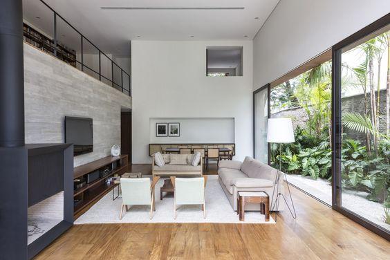 sala de estar ampla com vista para o jardim. Dentro temos: uma mesa de jantar ao fundo, sofás e cadeiras ao centro com uma tv na parede lateral. As paredes são brancas e o piso é porcelanato que imita madeira.