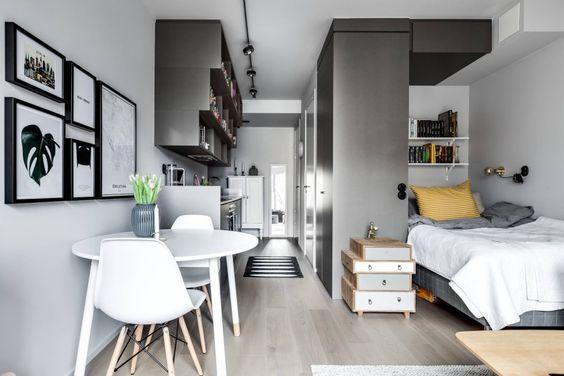 quarto e sala integrados, divido por um armário cinza e um criado mudo de madeira.  Lado esquerdo está a cozinha e direito o quarto. As paredes são brancas e o piso claro em porcelanato que imita madeira.