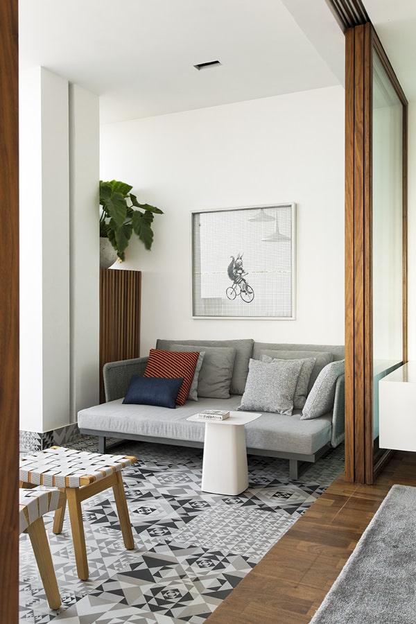 Sala de estar e varanda integradas e delimitadas através do revestimento de madeira na varanda e do porcelanato de efeito geométrico na sala de estar. Na sala de estar existe um sofá cinza, mesinha branca, bancos de madeira trançados e portas de vidro.