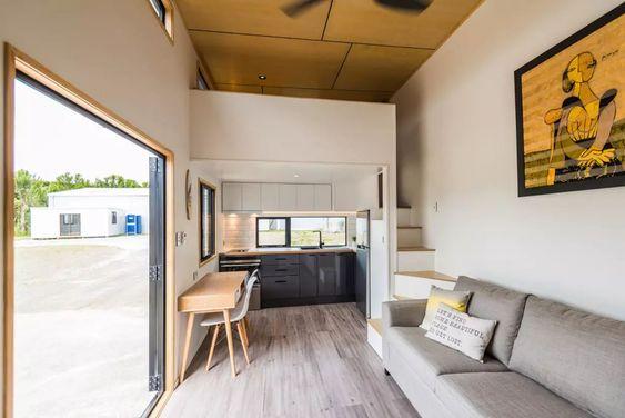 Espaço reduzido com sala e cozinha integrados. Decoração minimalista, com tons cinzas nos armários da cozinha e no sofá da sala. Ambos os espaços são revestidos com porcelanato acinzentado que imita madeira. A sala tem uma visão para área externa.