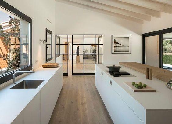 Cozinha minimalista, ampla, com visão para área externa. Presença de muito branco nas paredes e balcões, e para o revestimento um porcelanato que imita madeira clara.