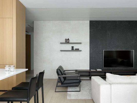 Sala de estar integrada com sala de jantar. Revestimento da parede em porcelanato branco e preto com efeito mármore. No piso, foi utilizado porcelanato que imita madeira. Os Moveis também são em preto e branco, como: sofá, poltronas, cadeiras e mesa.