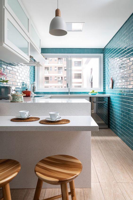 cozinha pequena com balcão e armários brancos, azulejos metrô em tom azul e piso de porcelanato claro que imita madeira.