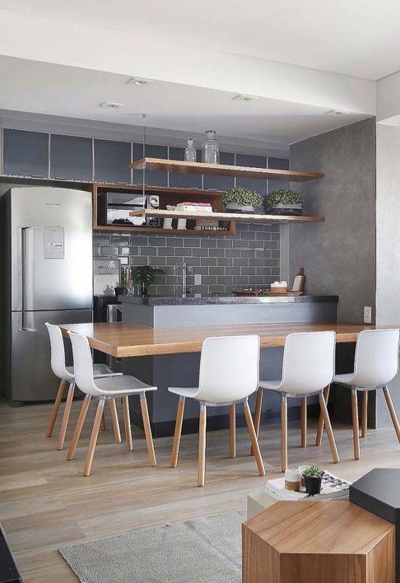 cozinha cinza com balcão de mármore, mesa de madeira, cadeiras brancas, azulejo subway cinza e porcelanato que imita madeira.