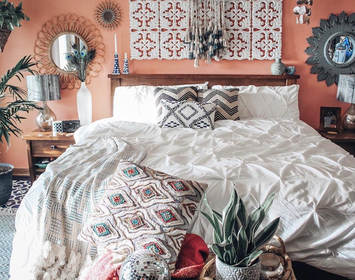 Quarto com estilo boho. Cama de madeira, almofadas étnicas, painel arabesco e espelhos arabescos.