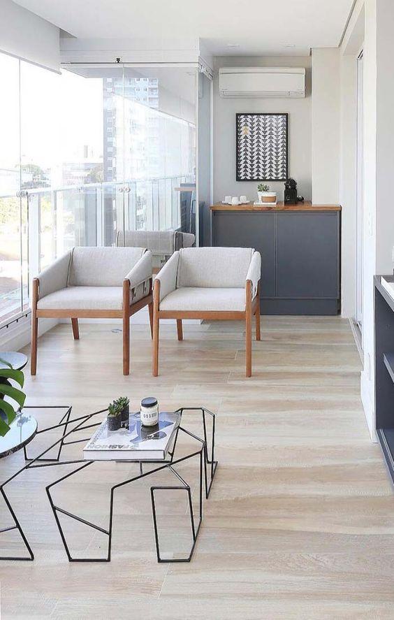Varanda com armários cinzas, duas cadeiras de madeira e uma mesa de centro moderna. O piso é porcelanato claro que imita madeira.