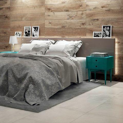 Quarto com uma cama em tom cinza, criados-mudos turquesas nas laterais e a cabeceira da cama em madeira. No revestimento, foram utilizados porcelanato claro no piso, e porcelanato que imita madeira nas paredes.