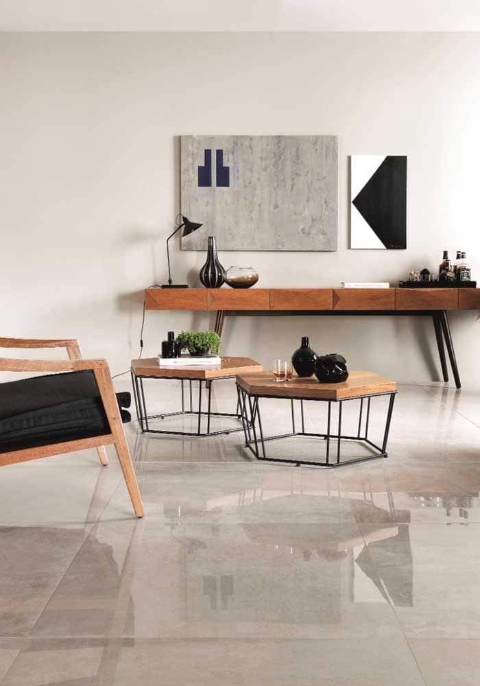 Sala de estar com porcelanato polido de formato grande. Nesta sala, existe: uma poltrona de madeira, duas mesinhas de madeira, e uma de mesa na parede do fundo com objetos.
