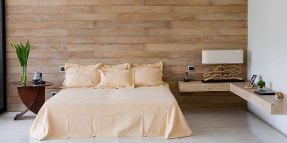 Quarto com cama no centro, mesa de madeira no lado esquerdo e uma escrivaninha de canto no lado direito. No revestimento, foram utilizados porcelanato que imita madeira na parede, e porcelanato claro no piso.